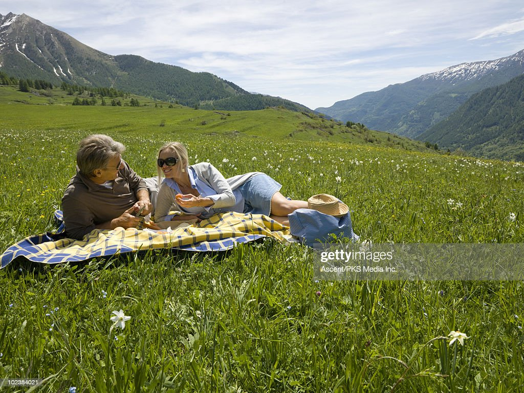 Couple share picnic in mountain meadow : Stock Photo
