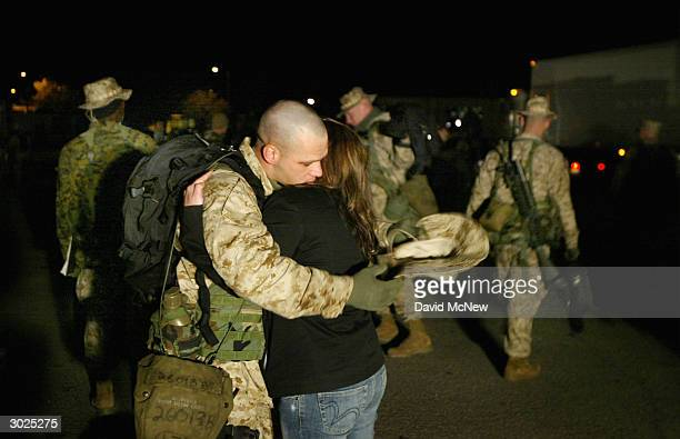 A couple shares a final hug as US Marines and sailors from 2nd Battalion 1st Marine Regiment based at Camp Pendleton walk to buses to deploy to the...
