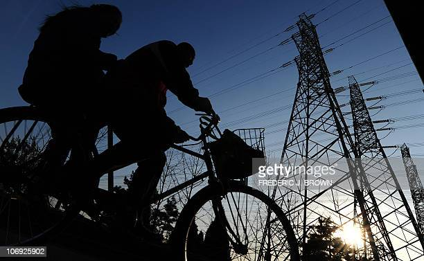 A couple sharing a bicycle ride past electricity pylons beneath an overpass in Beijing on November 15 2010 The spread of consumerism among China's...