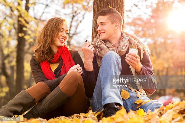 Couple sharing a song on MP3 player in autumn park.