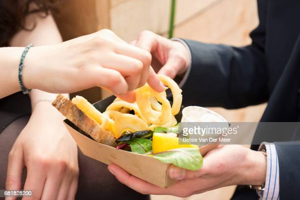 Couple sharing calamari dish, close up of hands picking out food.