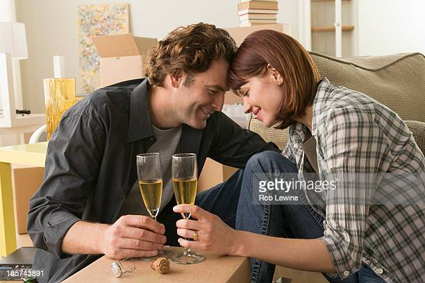Couple sharing champagne break whilst moving