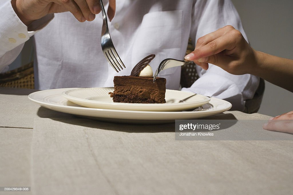 Couple sharing chocolate dessert at dining table, close-up : Stock Photo