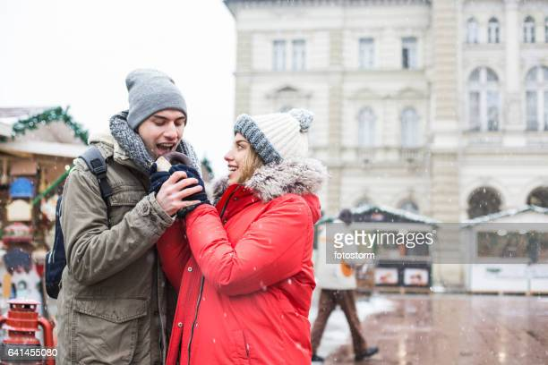 Couple sharing chocolate donut at winter market