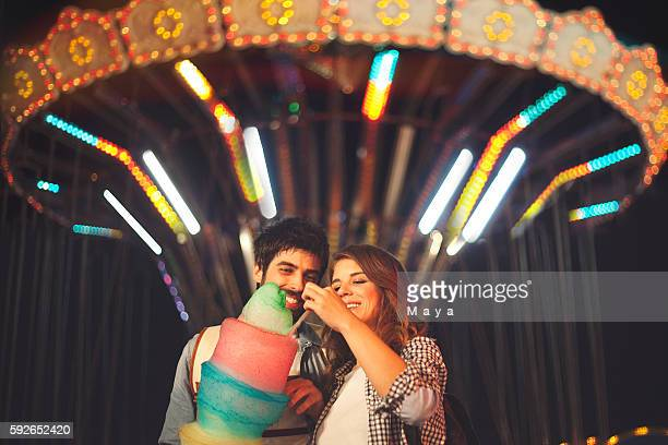Couple sharing cotton candy at fun fair