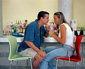 Couple sharing drink at bar