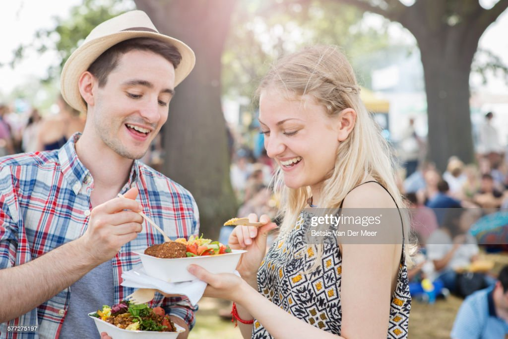 Couple sharing food at festival : Stock Photo