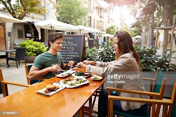 Couple sharing food at restaurant