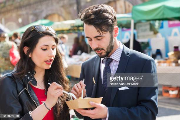 Couple sharing food dish standing in food market.