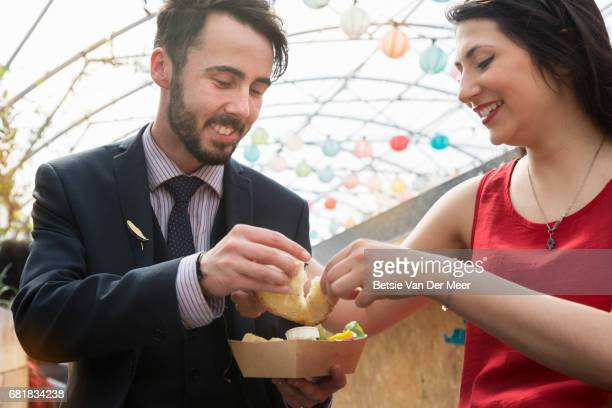 Couple sharing food in urban street food market.
