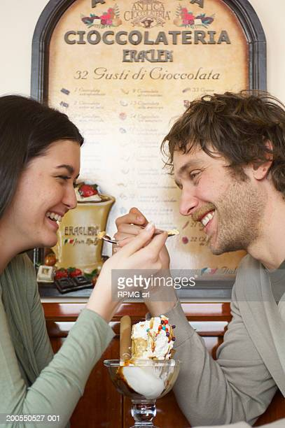 Couple sharing ice cream in cafe, side view