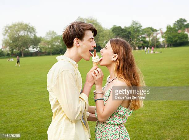 Couple sharing icecream in park.
