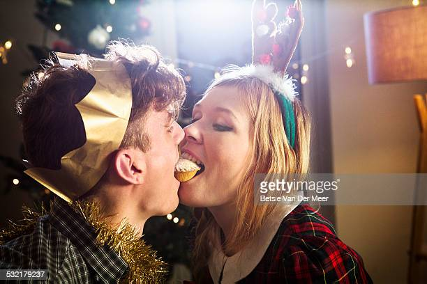 Couple sharing mince pie at Christmas.