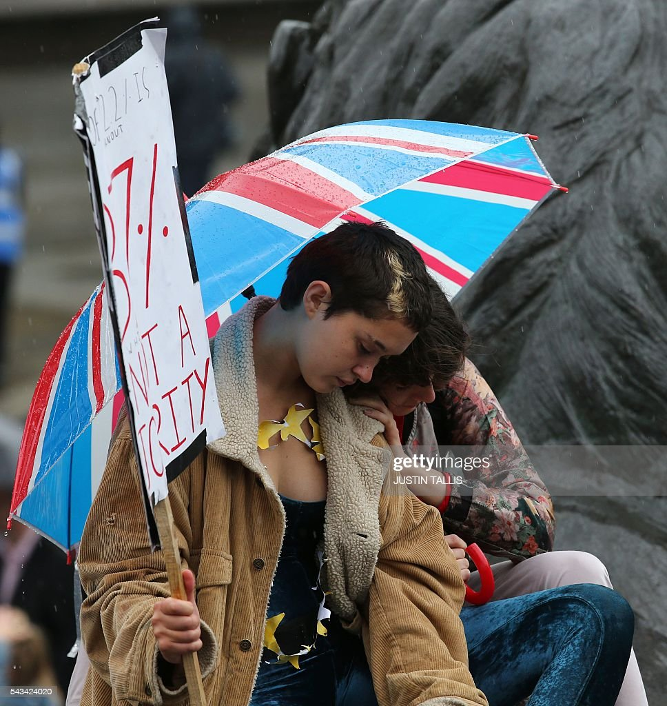 A couple shelter under a Union flag umbrella at an anti-Brexit protest in Trafalgar Square in central London on June 28, 2016. EU leaders attempted to rescue the European project and Prime Minister David Cameron sought to calm fears over Britain's vote to leave the bloc as ratings agencies downgraded the country. Britain has been pitched into uncertainty by the June 23 referendum result, with Cameron announcing his resignation, the economy facing a string of shocks and Scotland making a fresh threat to break away. / AFP / JUSTIN