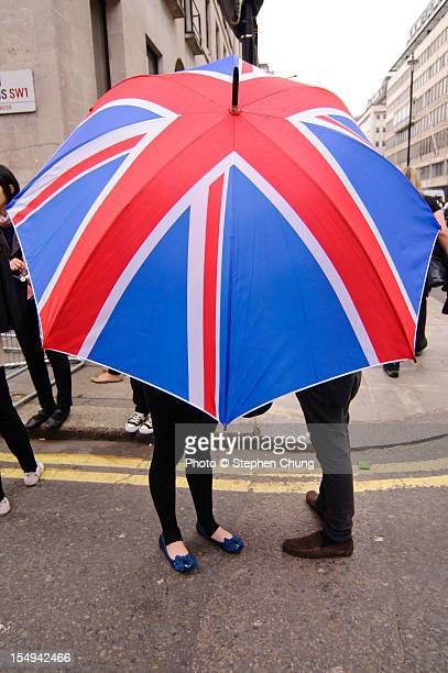 Couple shelter under a Union Jack umbrella