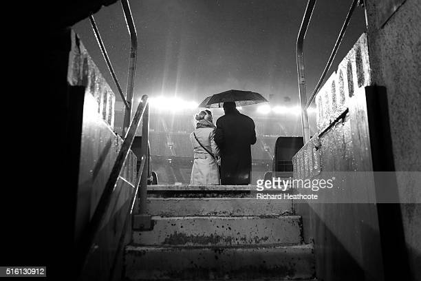 A couple shelter under an umbrella as rain falls prior to kick off during the UEFA Champions League Round of 16 Second Leg match between FC Barcelona...