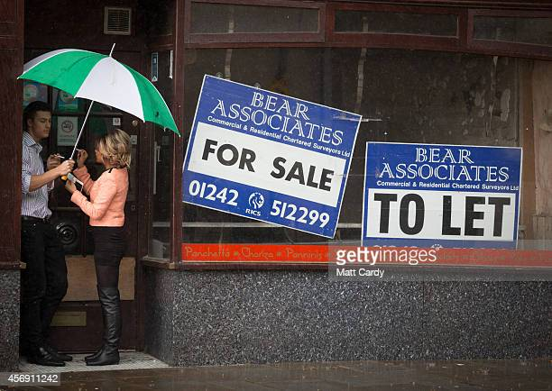 A couple shelter under an umbrella as they smoke a cigarette in the doorway of a empty shop on the high street on October 9 2014 in Gloucester...