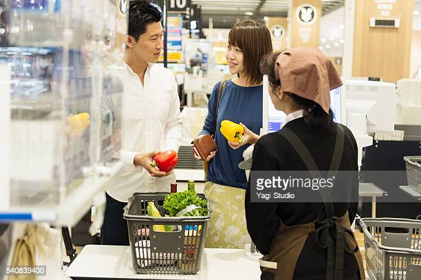 Couple shopping at the cash register of a supermarket