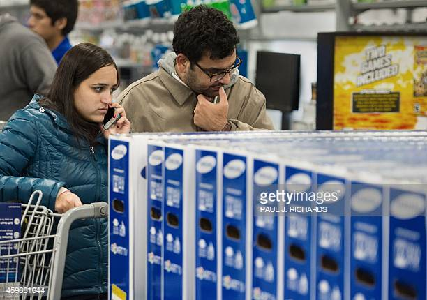 A couple shopping for a big screen TV call a friend shortly after the Black Friday doorbuster sale started on Thursday November 27 2014 at 500pm in...
