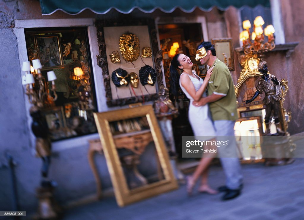Couple shopping for mask in Campo Santo Stefano, Venice, Italy