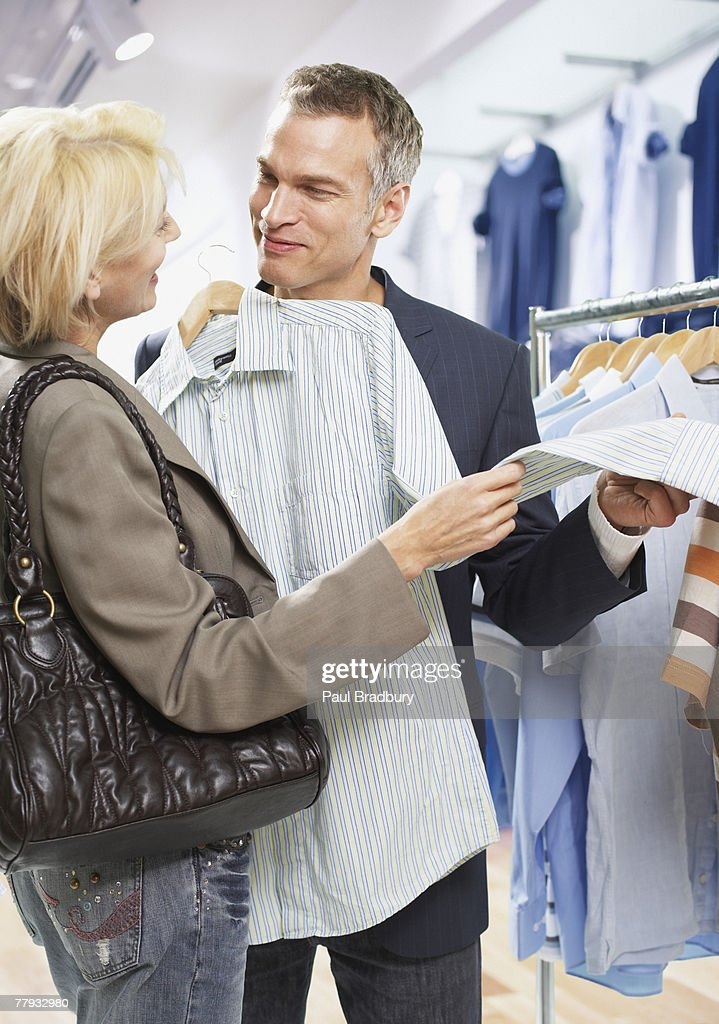 Couple shopping for shirts in store : Stock Photo