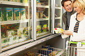 Couple shopping in freezer section in supermarket, smiling