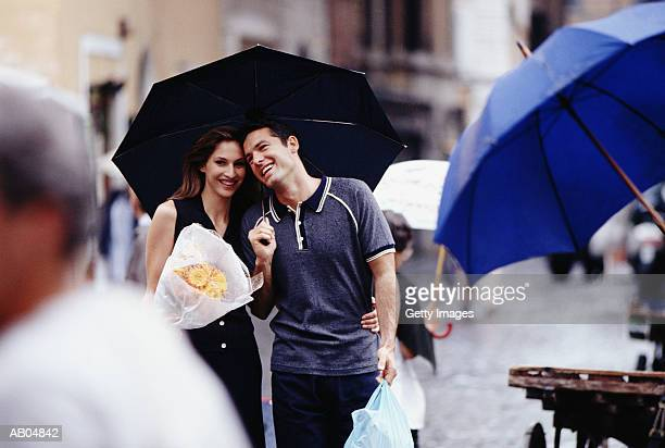Couple shopping in rain, Rome, Italy