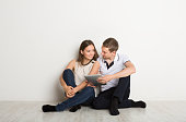 Couple shopping online, making order with digital tablet, sitting at home floor in empty living room
