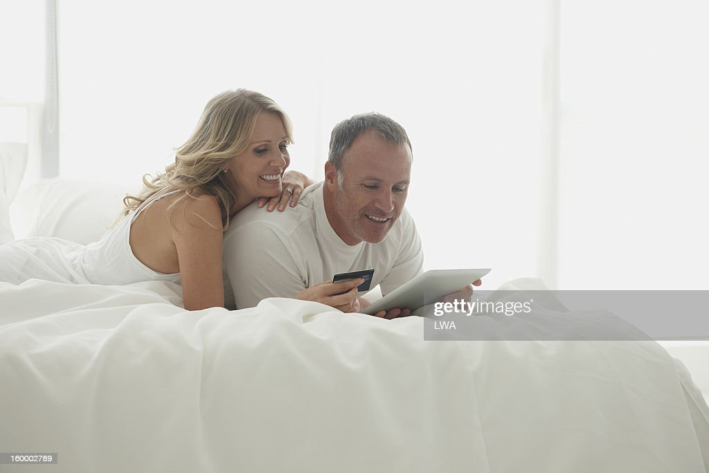 Couple shopping with digital tablet in bed : Stock Photo