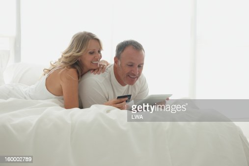 Couple shopping with digital tablet in bed : Foto stock
