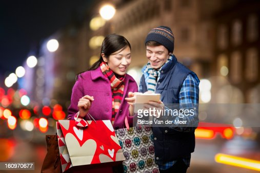 Couple shopping,looking at wireless device in city : Bildbanksbilder
