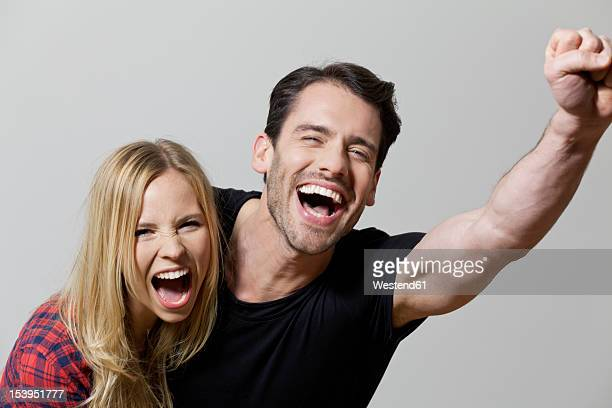 Couple shouting against white background, close up