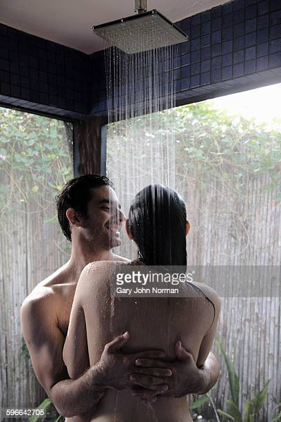 Couple showering together in outdoor shower.