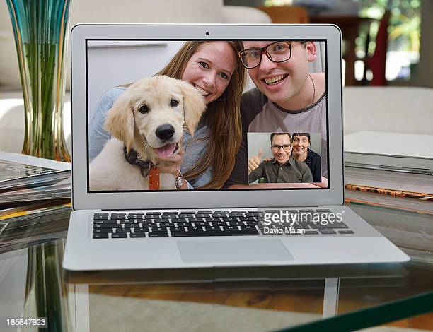 Couple showing off a new puppy over Skype.