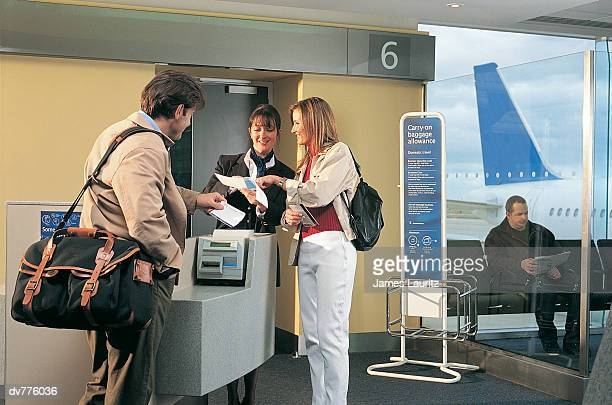 Couple Showing Their Tickets to an Air Stewardess in an Airport Lounge