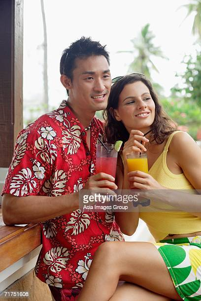 Couple side by side, holding drinks