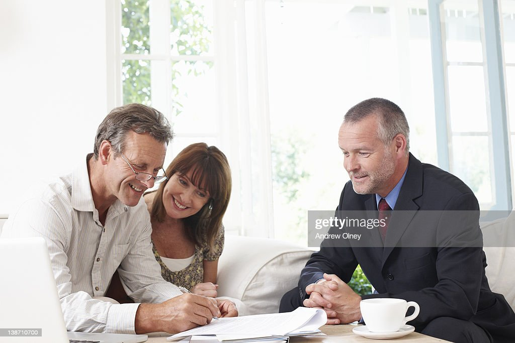 Couple signing contract with financial advisor : Stock Photo