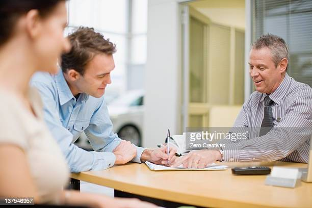Couple signing papers with car salesman