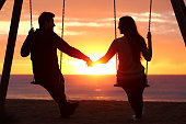 Back light portrait of a couple silhouette sitting on swing holding hands watching a sunrise on the beach with the sun in a warmth background