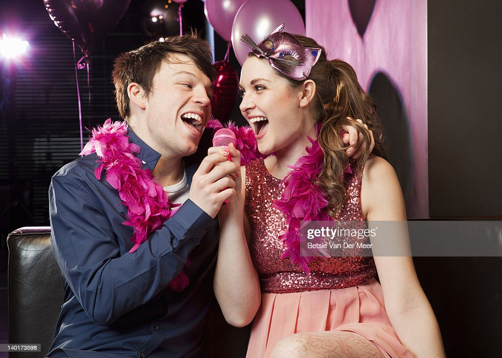 Couple singing karaoke in nightclub. : Stock Photo
