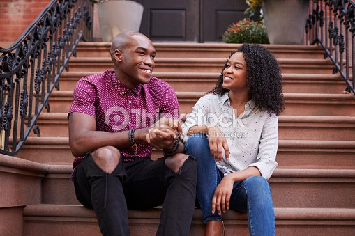 Couple Sit And Talk On Stoop Of Brownstone In New York City : Foto de stock