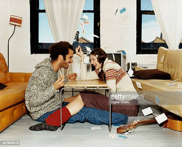 Couple Sit at a Table Playing a Card Game, Woman Throwing Playing Cards Into the Air