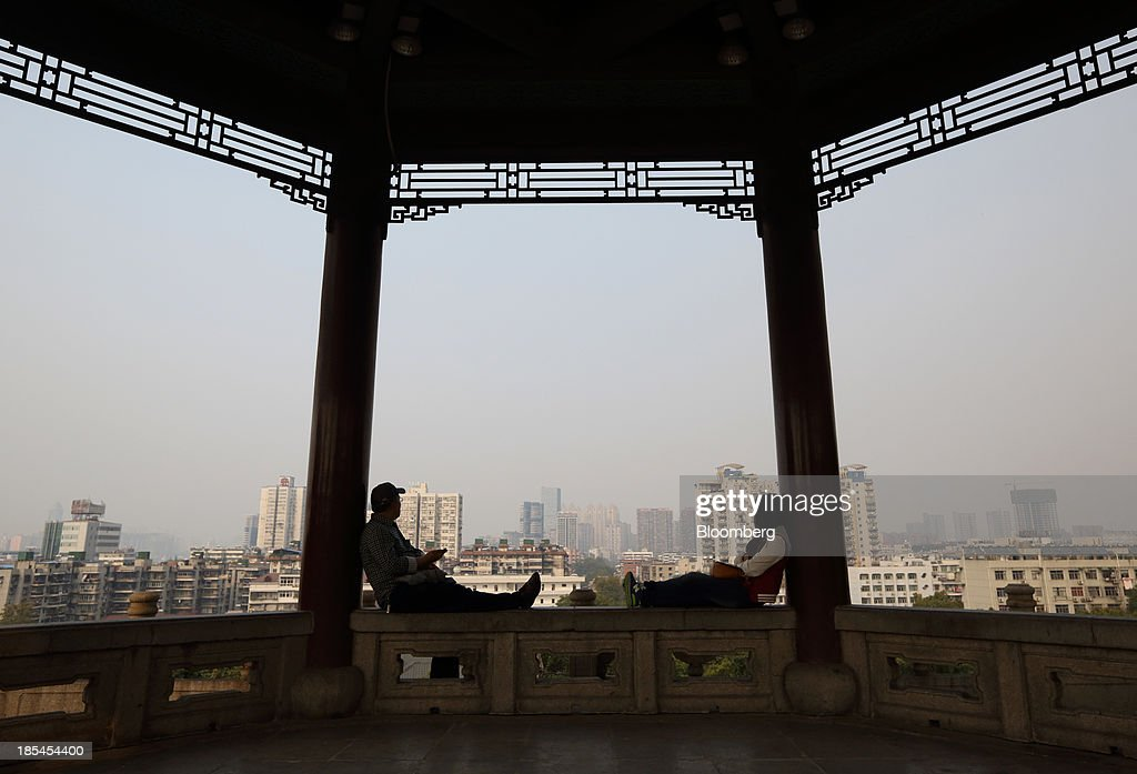 A couple sit at the Yellow Crane Tower in Wuhan, China, on Sunday, Oct. 20, 2013. China's economic expansion accelerated to 7.8 percent in the third quarter from a year earlier, the statistics bureau said Oct. 18, reversing a slowdown that put the government at risk of missing its 7.5 percent growth target for 2013. Photographer: Tomohiro Ohsumi/Bloomberg via Getty Images