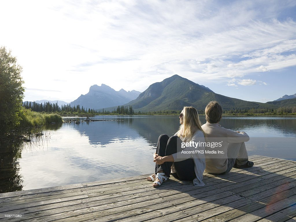 Couple sit back to back on mountain lake wharf : Stock Photo