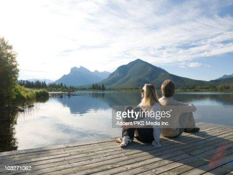 Couple sit back to back on mountain lake wharf : Stock Photo