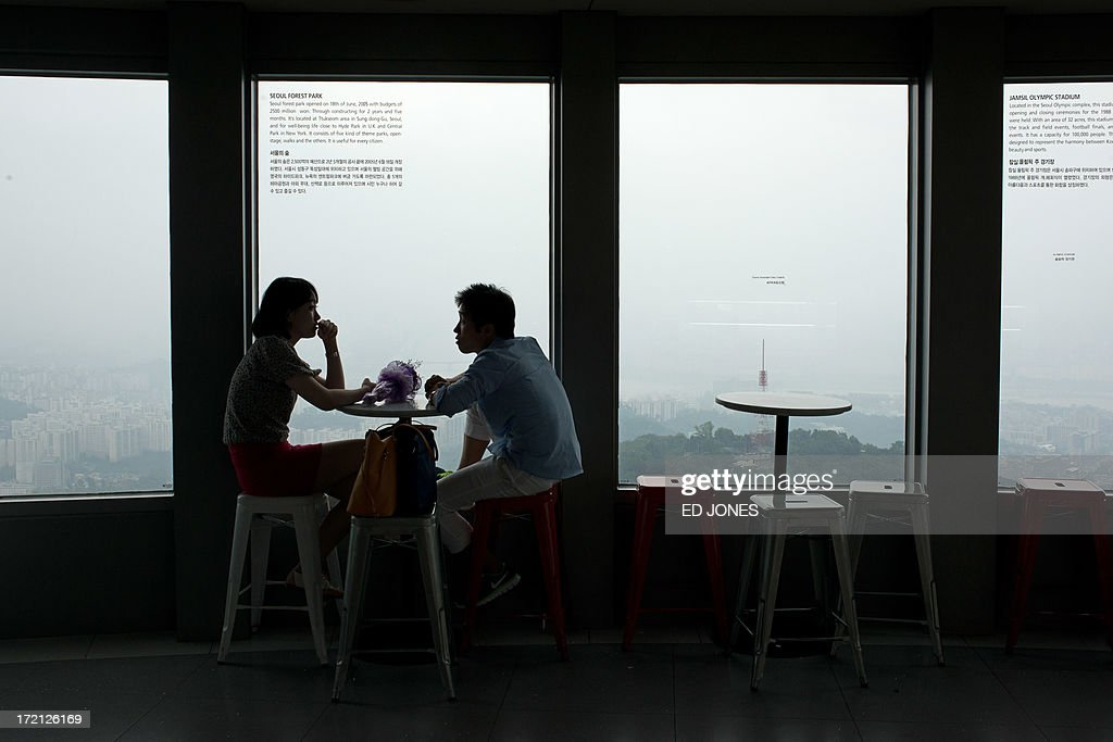 A couple sit before a window of the Namsan tower overlooking the Seoul city skyline during rainfall on July 2, 2013. July marks the wet season for Seoul during which the city of10 million people receives some 60 percent of its annual rainfall. AFP PHOTO / Ed Jones
