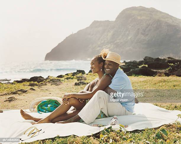 Couple Sit Embracing on a Picnic Blanket on Grass at the Coast