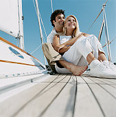 Couple Sit Embracing on the Deck of a Yacht, Looking at the View