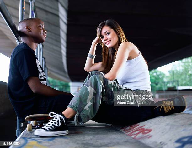 Couple Sit in a Skate Park, Girl Looking at Camera