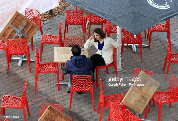 A couple sit in an outdoor cafe during the rain in Brighton Sussex as a yellow weather warning for rain has been issued for parts of the UK